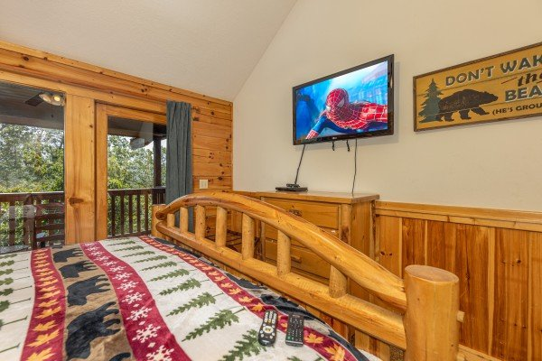 Dresser, TV, and deck access in a bedroom at Private Indulgences, a 2 bedroom cabin rental located in Gatlinburg