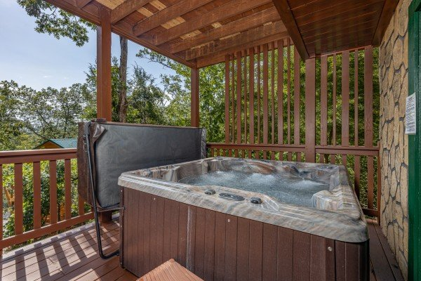 Hot tub on a covered deck at Private Indulgences, a 2 bedroom cabin rental located in Gatlinburg