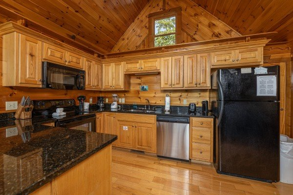 Kitchen with black and stainless appliances at Private Indulgences, a 2 bedroom cabin rental located in Gatlinburg