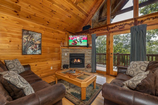 Two sofas, fireplace, TV, and deck access in a living room at Private Indulgences, a 2 bedroom cabin rental located in Gatlinburg