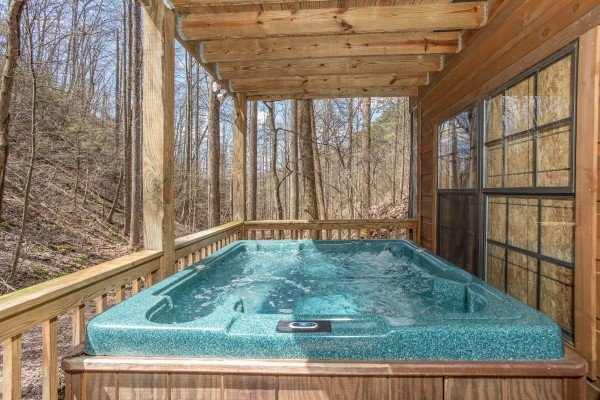Hot tub on a covered deck at My Smoky Mountain Hideaway, a 3 bedroom cabin rental located in Pigeon Forge