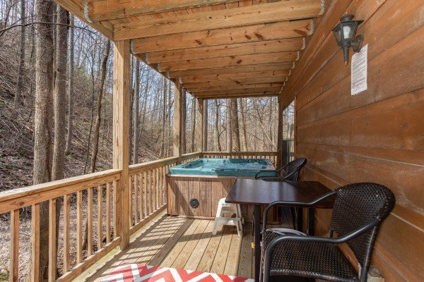 Hot tub and seating on a covered deck at My Smoky Mountain Hideaway, a 3 bedroom cabin rental located in Pigeon Forge