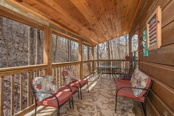 Seating on the upper covered deck at My Smoky Mountain Hideaway, a 3 bedroom cabin rental located in Pigeon Forge