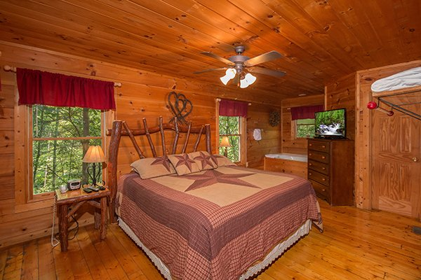 Bedroom with a king-sized log bed, dresser, and tv at Cabin Sweet Cabin, 1-bedroom cabin rental located in Gatlinburg