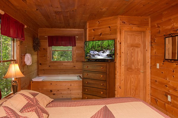 Jacuzzi tub and dresser with television in the bedroom at Cabin Sweet Cabin, 1-bedroom cabin rental located in Gatlinburg