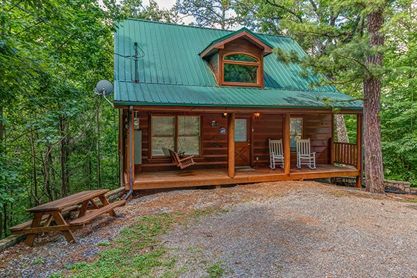 Exterior of the cabin with a picnic table and flat gravel parking at Cabin Sweet Cabin, 1-bedroom cabin rental located in Gatlinburg