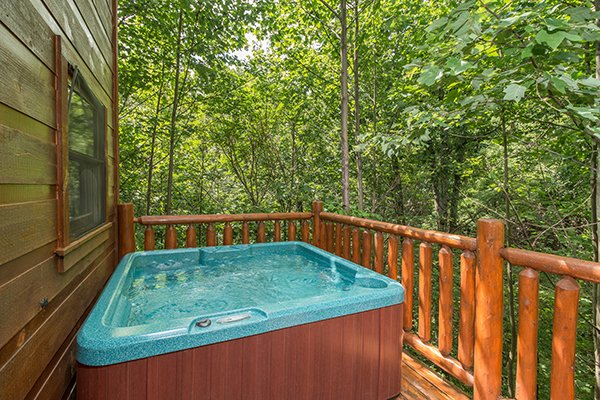 Hot tub on the deck surrounded by woods at Cabin Sweet Cabin, 1-bedroom cabin rental located in Gatlinburg