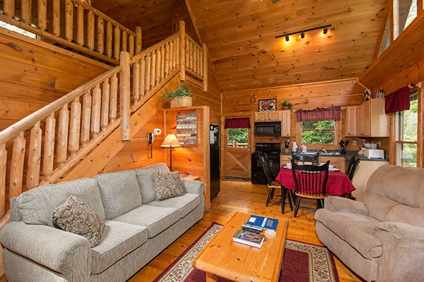 Sofa and chair in the living room, looking toward the dining area at Cabin Sweet Cabin, 1-bedroom cabin rental located in Gatlinburg