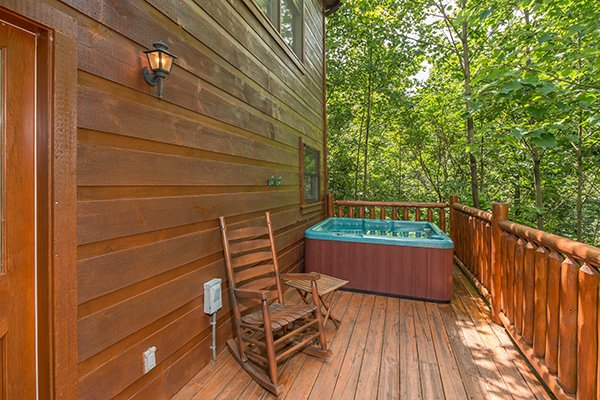 Hot tub and rocking chair on the deck at Cabin Sweet Cabin, 1-bedroom cabin rental located in Gatlinburg