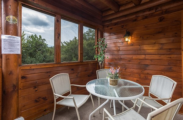 Dining space for four on the screened in deck at Mountain Escape, a 2 bedroom cabin rental located in Pigeon Forge