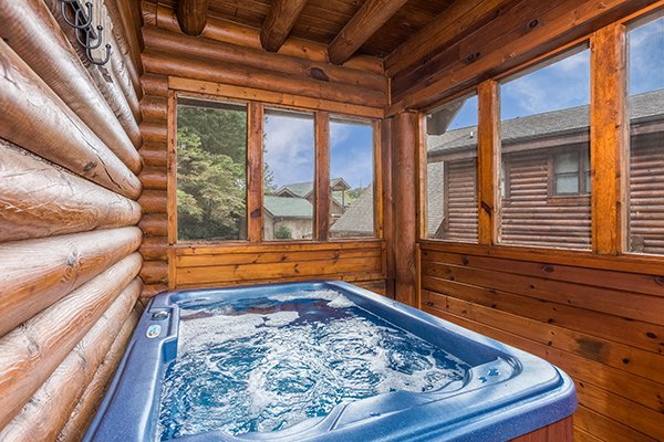 Hot tub on a screened in porch at Mountain Escape, a 2 bedroom cabin rental located in Pigeon Forge