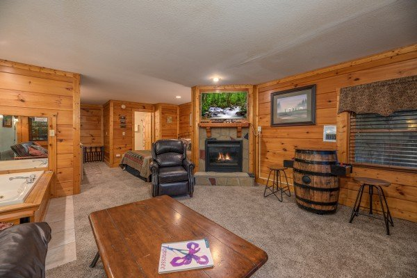 Lower living room with fireplace and TV at Mountain Escape, a 2 bedroom cabin rental located in Pigeon Forge