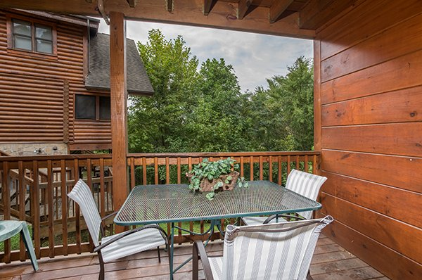 Dining space for three on the covered deck at Mountain Escape, a 2 bedroom cabin rental located in Pigeon Forge