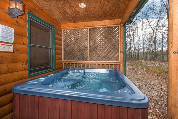 Hot tub on a covered porch at Lucky Logs, a 3 bedroom cabin rental located in Gatlinburg