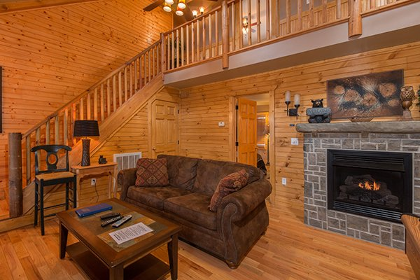 Fireplace and loveseat in the living room at Lucky Logs, a 3 bedroom cabin rental located in Gatlinburg