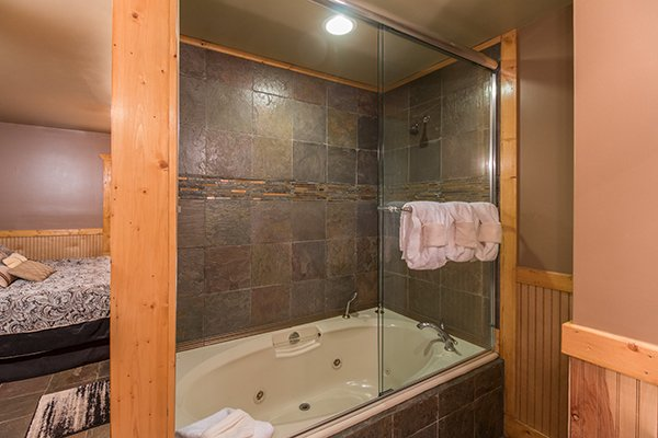 Jacuzzi tub and shower in the main floor bathroom at Lucky Logs, a 3 bedroom cabin rental located in Gatlinburg