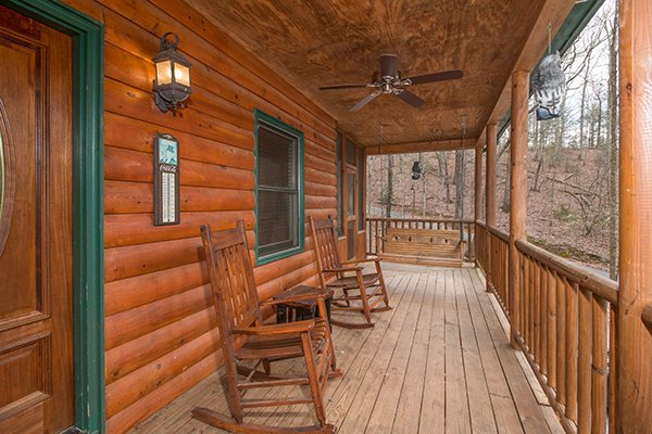 Covered porch with rocking chairs and a swing at Lucky Logs, a 3 bedroom cabin rental located in Gatlinburg