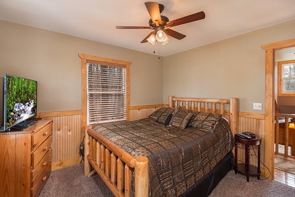 Bedroom with a queen bed, dresser, and TV at Lucky Logs, a 3 bedroom cabin rental located in Gatlinburg