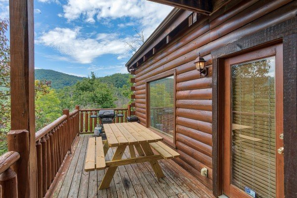 Deck dining table and grill at Over the Rainbow, a 3 bedroom cabin rental located in Pigeon Forge