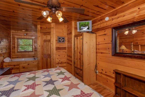 Bedroom with an armoire, TV, and jacuzzi at Over the Rainbow, a 3 bedroom cabin rental located in Pigeon Forge