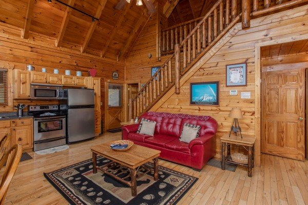 Sofa and kitchen with stainless steel appliances at Over the Rainbow, a 3 bedroom cabin rental located in Pigeon Forge