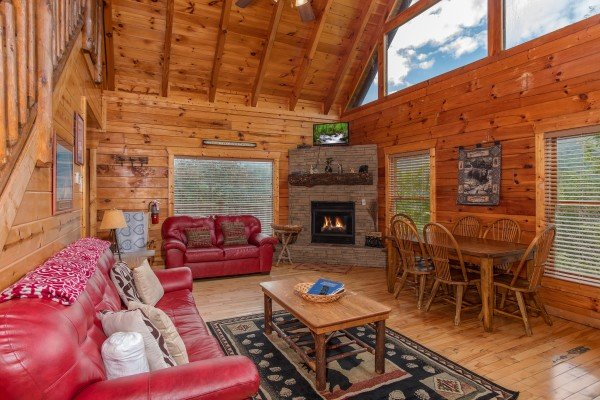 Living room with fireplace and dining table for six at Over the Rainbow, a 3 bedroom cabin rental located in Pigeon Forge