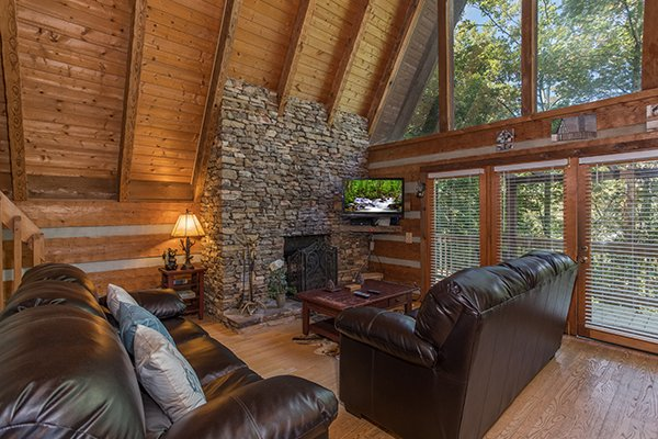 Living room with stone fireplace and TV at Soaring Heights, a 3 bedroom cabin rental located in Gatlinburg