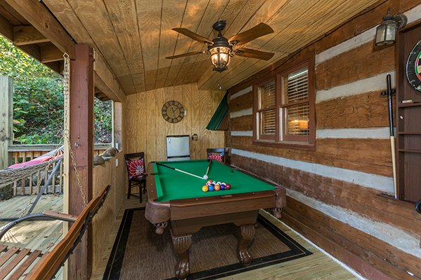 Pool table on a covered deck at Soaring Heights, a 3 bedroom cabin rental located in Gatlinburg