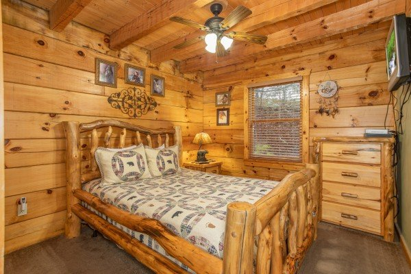 Bedroom with a queen sized log bed, dresser, and TV at Alpine Romance, a 2 bedroom cabin rental located in Pigeon Forge