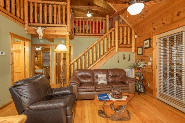 Living room with a large chair and sofa at Alpine Romance, a 2 bedroom cabin rental located in Pigeon Forge