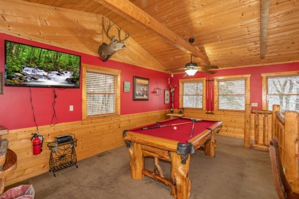 Red felt pool table and TV in the game loft at Alpine Romance, a 2 bedroom cabin rental located in Pigeon Forge