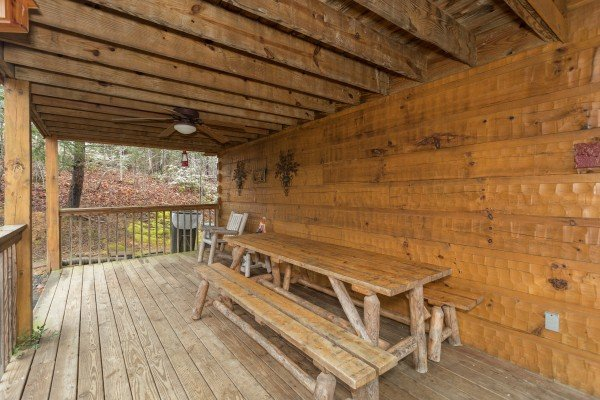 Picnic table on a covered deck at Alpine Romance, a 2 bedroom cabin rental located in Pigeon Forge
