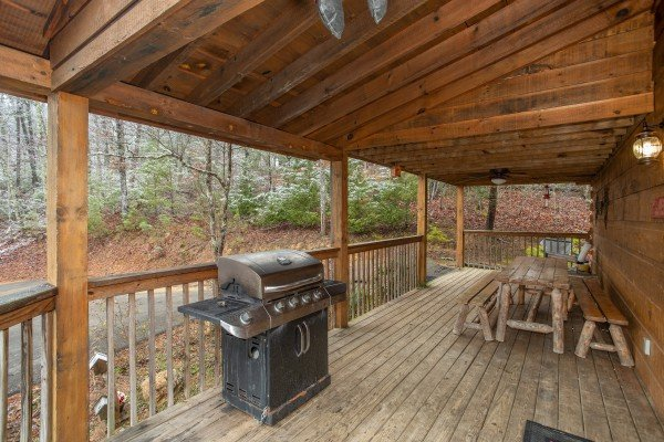Propane grill and picnic table on a covered deck at Alpine Romance, a 2 bedroom cabin rental located in Pigeon Forge