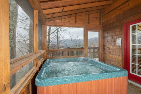 Hot tub on a screened in porch at Alpine Romance, a 2 bedroom cabin rental located in Pigeon Forge