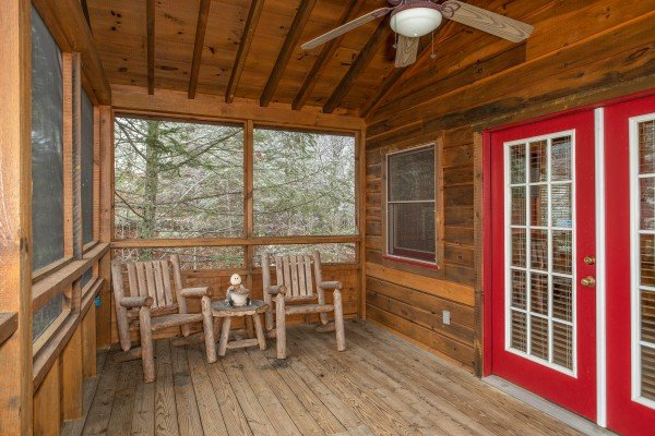 Two chairs on the screened in porch at Alpine Romance, a 2 bedroom cabin rental located in Pigeon Forge