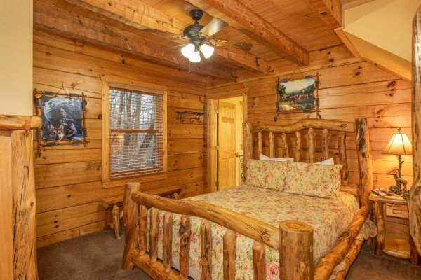 Bedroom with a queen size log bed at Alpine Romance, a 2 bedroom cabin rental located in Pigeon Forge