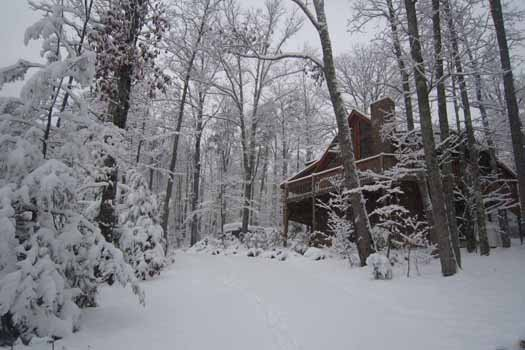 snow covered trees surround a log cabin named alpine romance a 2 bedroom cabin rental located in pigeon forge