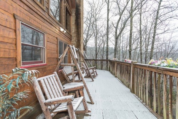A dusting of snow on a log chair and porch swing at Alpine Romance, a 2 bedroom cabin rental located in Pigeon Forge