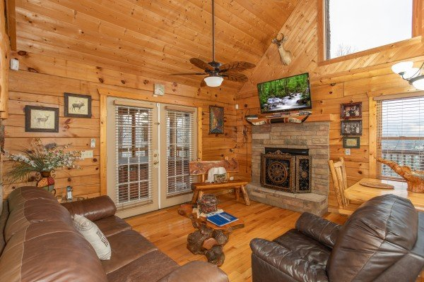Living room with vaulted ceiling, fireplace, and TV at Alpine Romance, a 2 bedroom cabin rental located in Pigeon Forge