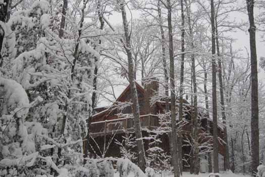 looking up at a snow covered log cabin named alpine romance a 2 bedroom cabin rental located in pigeon forge