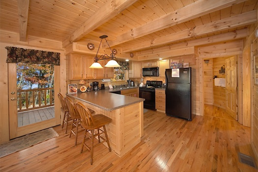 kitchen and breakfast bar at paws n' claws a 2 bedroom cabin rental located in gatlinburg