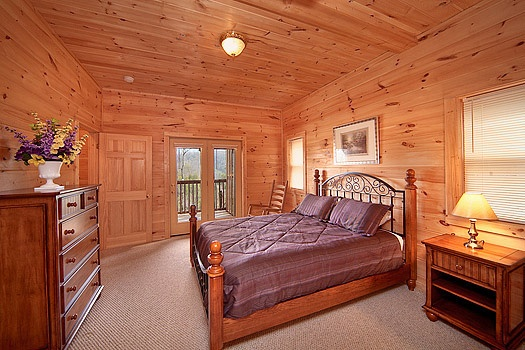 Queen sized bed in a first floor bedroom with patio doors to deck at Highlander, a 4 bedroom cabin rental located in Gatlinburg