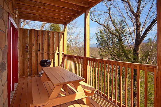 picnic table and charcoal grill on the deck at highlander a 4 bedroom cabin rental located in gatlinburg