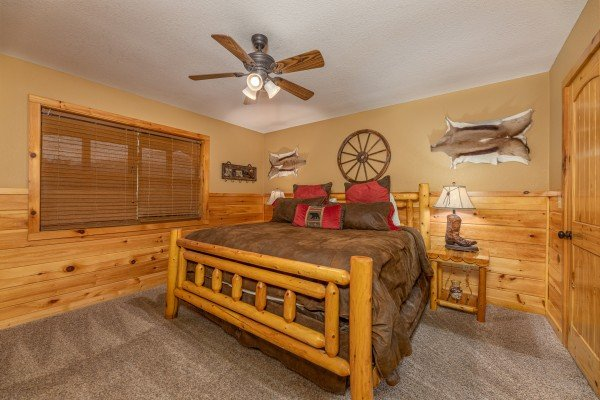 Bedroom with a king bed, two night stands, and lamps at Rainbow's End, a 4 bedroom cabin rental located in Pigeon Forge