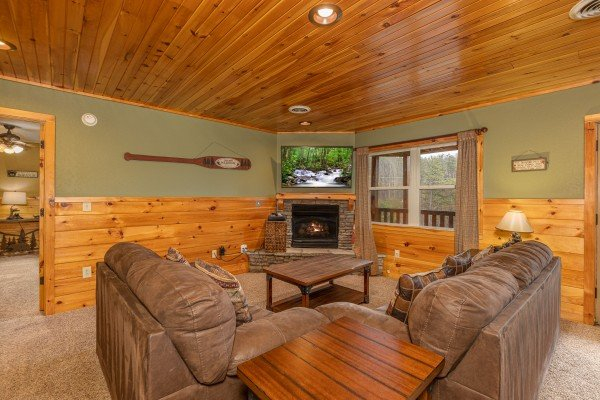 Living room with fireplace and TV downstairs at Rainbow's End, a 4 bedroom cabin rental located in Pigeon Forge