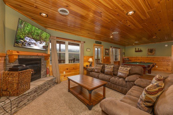 Two sofas, a fireplace, and tv in the lower living room at Rainbow's End, a 4 bedroom cabin rental located in Pigeon Forge