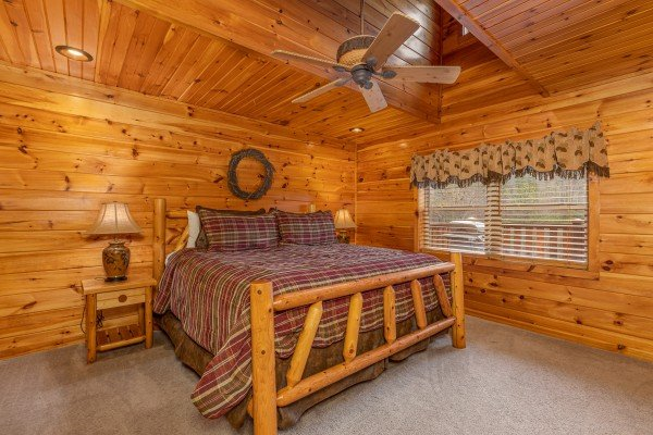 Bedroom with a log bed, two night stands, and lamps at Rainbow's End, a 4 bedroom cabin rental located in Pigeon Forge