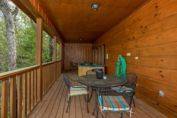 Dining area and hot tub on a covered porch at Hillside Haven, a 1 bedroom cabin rental located in Pigeon Forge