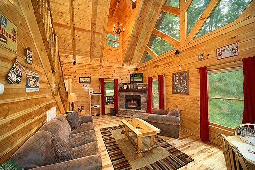 living room with sofa bed and stone fireplace at brownie bear a 1 bedroom cabin rental located in gatlinburg