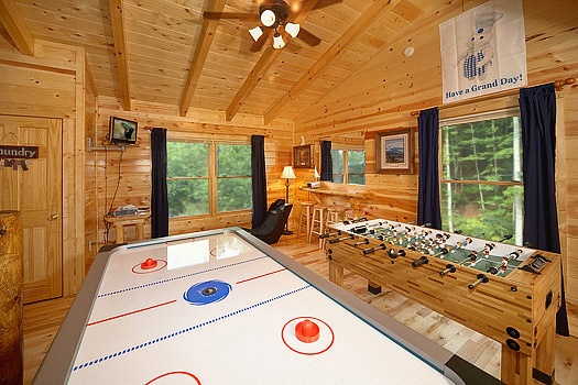 Lofted game room with air hockey, ping pong, and foosball tables at Brownie Bear, a 1-bedroom cabin rental located in Gatlinburg